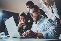 Proceso de la reunión de reflexión del trabajo en equipo Hombre joven que trabaja así como socios en desván moderno de la oficina imagen de archivo