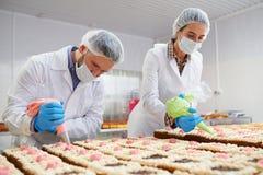 Proceso de las tortas que adornan en fábrica fotos de archivo