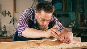 Proceso de medición de madera celebrado por un carpintero Artesano que trabaja en carpintería almacen de metraje de vídeo