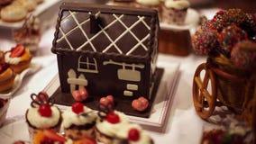 Proceso de panadería de la Navidad, decoración de la Navidad, pasteles casa de pan de jengibre en la tabla almacen de video