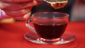 Proceso de preparar té negro Mujer que presiona la bolsita de té con la ayuda de la cuchara metrajes