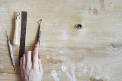Proceso de trabajo de cerámica, herramientas para el trabajo mano-hecho a mano en mano de la mujer Visión desde arriba, tabla de  Imagen de archivo