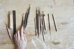 Proceso de trabajo de cerámica, herramientas para el trabajo mano-hecho a mano en mano de la mujer Visión desde arriba, tabla de  Fotos de archivo libres de regalías