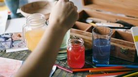 Proceso de trabajo del artista vidrios de los envases con agua la mano con un cepillo disuelve la pintura verde de la acuarela Im almacen de metraje de vídeo