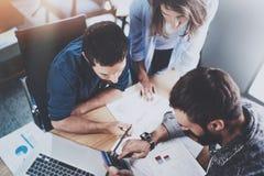 Proceso de trabajo del trabajo en equipo Grupo de compañeros de trabajo jovenes que trabajan junto en desván moderno de la oficin imagen de archivo