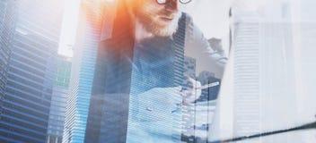 Proceso de trabajo del hombre de negocios en la oficina moderna Compañero de trabajo joven que trabaja en la tabla de madera con  foto de archivo