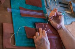 Proceso de trabajo de la cartera de cuero en el taller de cuero imagen de archivo