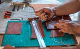 Proceso de trabajo de la correa de cuero en el taller de cuero Hombre que celebra hacer la herramienta a mano y el trabajo Tanner fotos de archivo libres de regalías