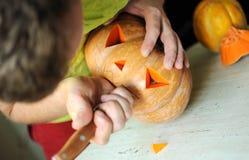Proceso del corte de la calabaza de Halloween, proceso de hacer la Jack-o-linterna Manos masculinas con el cuchillo Imágenes de archivo libres de regalías