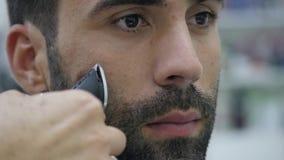 Proceso del Hairstyling Primer de un cabello seco del peluquero de un hombre barbudo joven metrajes