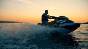 proceso del Jet-esquí de un hombre durante puesta del sol hermosa almacen de metraje de vídeo