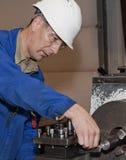 proceso del metal El trabajador trabaja en un torno Imagen de archivo libre de regalías