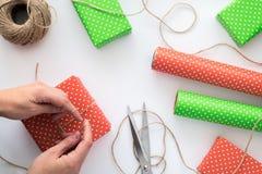 Proceso del paquete y de envolver caja de regalo de la Navidad y del Año Nuevo con las manos de la mujer Papel de embalaje, tijer Fotografía de archivo libre de regalías