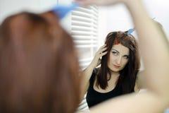 Proceso del pelo que muere en casa Mujer que mira en el espejo imagenes de archivo