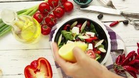 Proceso griego de la preparación de la ensalada: un cocinero exprime el limón para añadir el jugo de limón almacen de metraje de vídeo