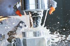 Proceso que muele CNC de la precisión que trabaja a máquina por el molino vertical con el líquido refrigerador fotos de archivo