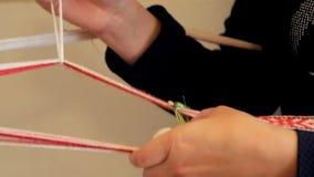 Proceso veawing de la mano Armadura de la tela con la herramienta de mano Fabricación de la materia textil almacen de metraje de vídeo