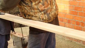 Process with angle grinder. Grinding of a wooden board 20 mm for the manufacture of furniture and shelves. An old man is. Working in the open air. Carpentry as stock video footage