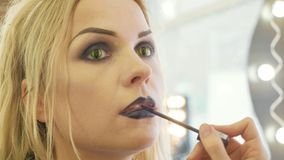 Process applying halloween makeup on face the young beautiful woman. Process applying halloween makeup on face the young beautiful blonde woman contact lenses as Royalty Free Stock Photos