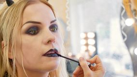 Process applying halloween makeup on face the young beautiful woman stock photography