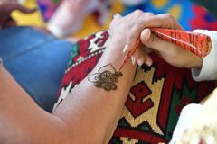 Mehndi henna tattoo. A henna or mehendi applier at work royalty free stock photos