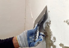 The process of applying a white putty on concrete gray wall Stock Photo