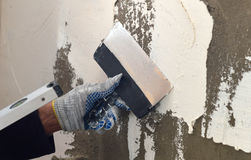 The process of applying a white putty on concrete gray wall Royalty Free Stock Photo