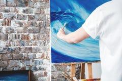 Process av att dra ett konstnärarbete i flåsandestudio Målarehållmålarpensel i hand framme av kanfas på staffli hobby royaltyfria bilder