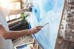 Process av att dra ett konstnärarbete i konstvindstudio med oilpaints Målarehållmålarpensel i hand framme av kanfas på staffli arkivbild