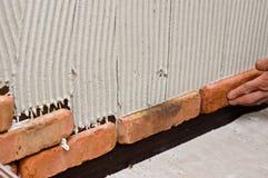 Process av att göra en vägg för röd tegelsten, hem- renovering Fotografering för Bildbyråer