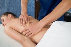 Process av att göra tillbaka massage till den avkopplade kvinnliga klienten arkivfoton