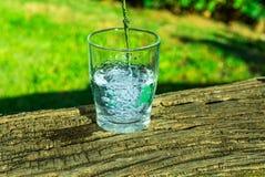 Process av att hälla rent klart vatten in i ett exponeringsglas från överkanten, träjournal, grönt gräs i bakgrunden, utomhus, hä arkivbilder