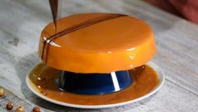 Process av att skapa den läckra kakan Oigenkännliga konditorhänder dekorerar den karamell glasade kakan med choklad stock video
