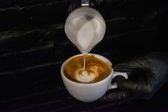 Process av förberedelsen av en cappuccino med lattekonst Arbeta baristaen i coffee shop Svart bakgrund och handskar Nytt kaffe arkivbild
