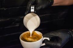 Process av förberedelsen av en cappuccino med lattekonst Arbeta baristaen i coffee shop Svart bakgrund och handskar Nytt kaffe royaltyfria bilder