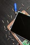 Process av reparationen för PCminnestavlaapparat nära skruvmejseln och biten på svart träbakgrund demontert Brutet exponeringsgla arkivbilder
