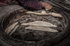 The process of baking bread in a traditional Georgian stove - to Stock Photo