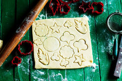 Process of baking cookies at home. Fresh dough ready for baking on rustic green wooden background. Dough ingredients and decoratio Stock Image