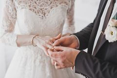 The process of betrothal of newlyweds 1217. Husband puts his wife`s wedding ring on the ring finger stock photo
