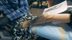 Process of bionic prosthesis tattooing, disabled man. 4K stock video