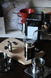 The process of brewing coffee. Pour water from the drip maker into the french press. Pack with white label Stock Images