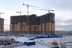 The process of building a large multi-storey residential building in the winter. The work of construction cranes. Half built house stock photos