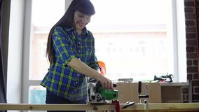 Woman carpenter saws wooden bar using circular electric saw in workshop. The process of building a wooden table, a woman carpenter saws a wooden bar using a stock footage