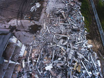 A process of buliding demolition, demolished house, shot from air with drone. A process of buliding demolition, demolition site with heavy bulldozer and Royalty Free Stock Image