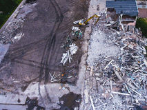 A process of buliding demolition, demolished house, shot from air with drone. A process of buliding demolition, demolition site with heavy bulldozer and Royalty Free Stock Images