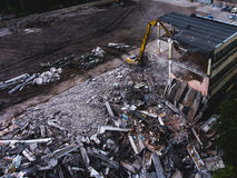 A process of buliding demolition, demolished house, shot from air with drone. A process of buliding demolition, demolition site with heavy bulldozer and Royalty Free Stock Photos