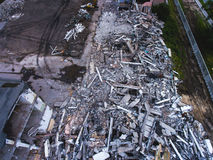 A process of buliding demolition, demolished house, shot from air with drone. A process of buliding demolition, demolition site with heavy bulldozer and Stock Photography
