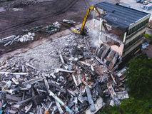 A process of buliding demolition, demolished house, shot from air with drone. A process of buliding demolition, demolition site with heavy bulldozer and Royalty Free Stock Photography