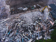 A process of buliding demolition, demolished house, shot from air with drone. A process of buliding demolition, demolition site with heavy bulldozer and Stock Images