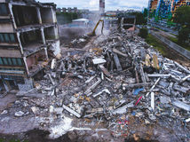 A process of buliding destruction, demolished house, shot from air with drone. A process of buliding destruction, demolition site with heavy bulldozer and Royalty Free Stock Photo